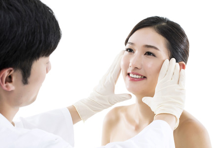 Photo for Plastic Surgery/ Doctor Examining the Face of a Young Asian Woman - Royalty Free Image