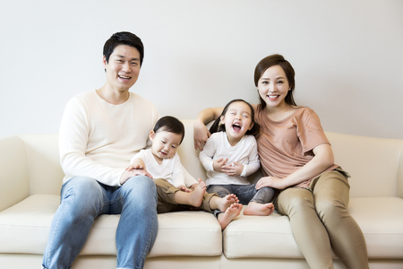 Photo for Happy Asian Family Smiling on the Sofa at Home - Royalty Free Image
