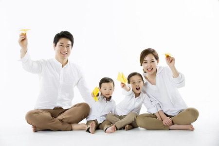 Photo for Happy Family Flying Yellow Paper Plane - Isolated on White - Royalty Free Image