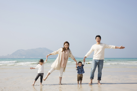 Happy Asian Family Holding Hands and Walking on Beach