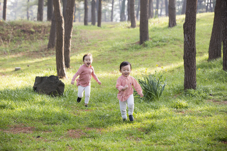 Photo for Cute Asian Boy and Girl Laughing and Running on Grass in Forest - Royalty Free Image