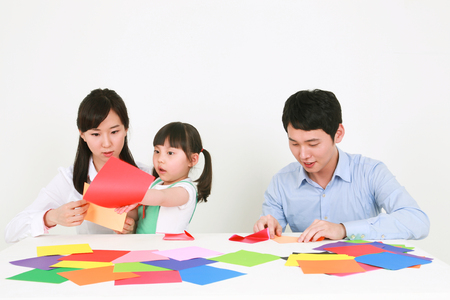 Photo pour Adults and a little girl folding colored paper - isolated on white - image libre de droit