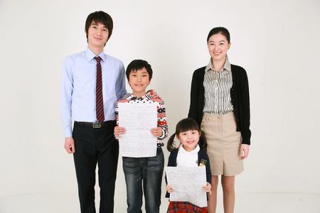 Photo pour Two teachers and two little boys holding up a test paper - image libre de droit