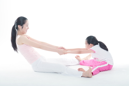 Foto de Young Asian mom and her little daughter doing yoga poses together - isolated on white - Imagen libre de derechos