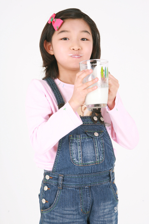 Foto de A asian girl drinking with glass of milk - isolated on white - Imagen libre de derechos