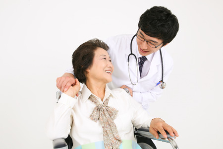 Photo for A male doctor eyecontacting with the senior patient sitting in wheelchair - Royalty Free Image