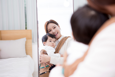 Photo for Working mom with the baby looking at the mirror in the room - Royalty Free Image