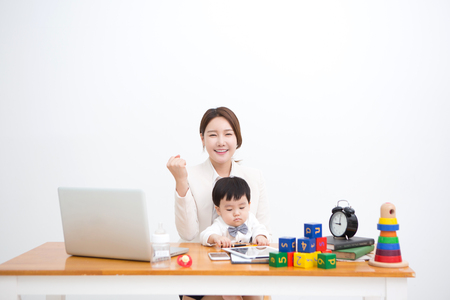 Foto de Working mom with the baby sitting on the desk with toys - isolated on white - Imagen libre de derechos