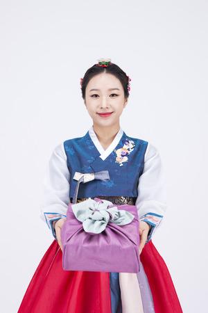 Foto de Young Asian woman in Hanbok, Korean traditional clothes, posing with a gift - isolated on white - Imagen libre de derechos