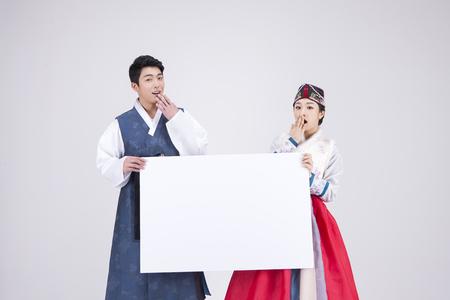 Foto de Young Asian couple in Hanbok, Korean traditional clothes, holding a blank board - isolated on white - Imagen libre de derechos