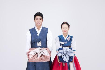 Foto de Young Asian couple in Hanbok, Korean traditional clothes, posing with gift boxes - isolated on white - Imagen libre de derechos