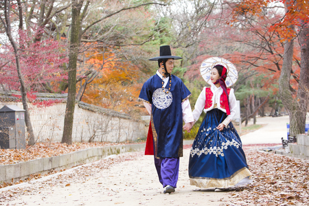 Photo for Young Asian newlywed couple in Hanbok, Korean traditional clothes walking around Hanok, Korean traditional house - Royalty Free Image
