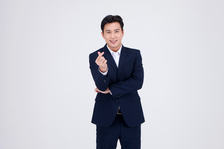 Photo pour Isolated shot in white of Asian man in business suit - making/doing hand gestures - image libre de droit