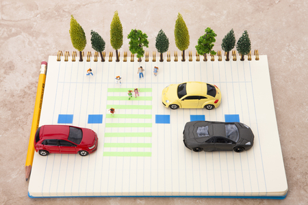 Photo for Creative miniature life - Kids crossing the crosswalk and cars at the stop lines - Royalty Free Image