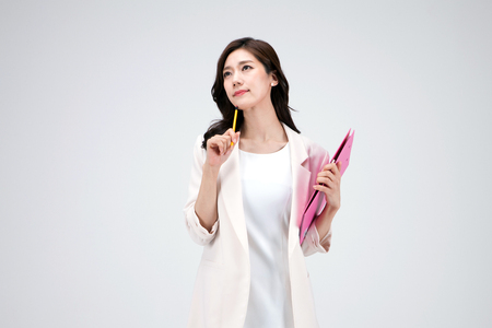 Photo for Isolated shot in studio - Asian career woman in white dress holding a file folder - Royalty Free Image