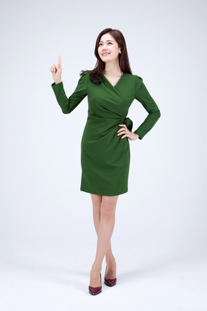Foto de Isolated shot in studio - Asian career woman in green dress posing with hand gestures - Imagen libre de derechos