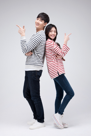 Photo for Isolated shot in studio - Asian young couple wearing matching shirts posing together - Royalty Free Image