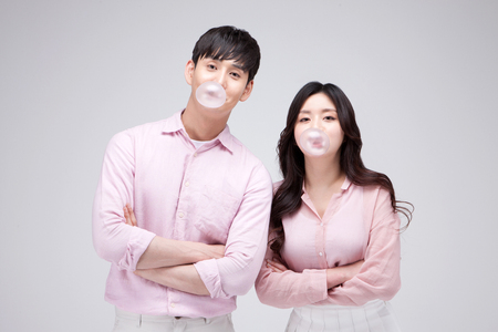 Foto de Isolated shot in studio - Asian young couple wearing matching outfits blowing bubble gum - Imagen libre de derechos