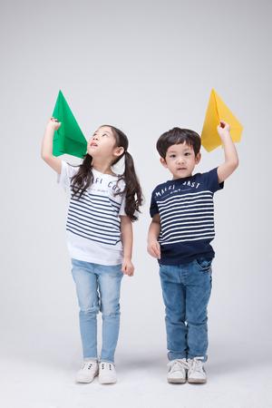 Foto de Isolated shot in studio - little Asian girl and boy posing with various props - Imagen libre de derechos