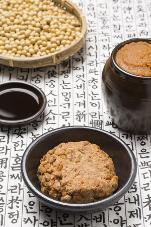 Photo for Doenjang(Korean soybean paste), Cheonggukjang(Korean fast-fermented bean paste), soy sauce and soybeans on Korean paper - Royalty Free Image