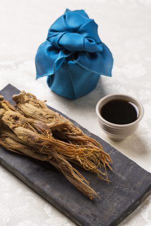 Foto de dried red ginseng,on a Korean traditional tile, red ginseng extract and gift wrapped with blue silk - Imagen libre de derechos