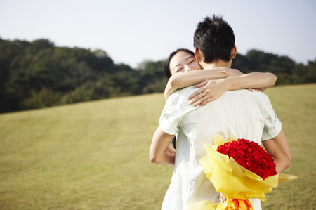 Photo pour Asian couple posing together in a green field with a bouquet of red roses - image libre de droit