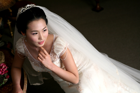 Photo pour Close up shot of Asian bride in wedding dresses posing in a studio as sitting on chair - image libre de droit