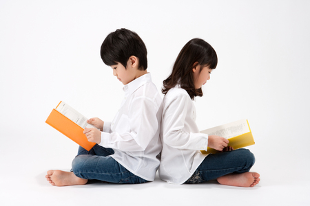 Foto de Asian boy and girl reading book leaning against each other back to back isolated on white - Imagen libre de derechos