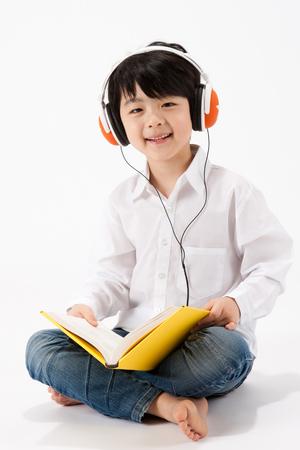 Foto de Asian boy reading book with headphone isolated on white - Imagen libre de derechos