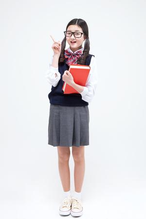 Foto de Asian smart middle school girl with book isolated on white - Imagen libre de derechos