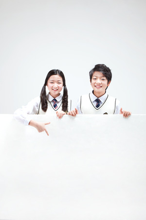Photo for Portrait of Asian middle school boy and girl behind big white board isolated on white - Royalty Free Image