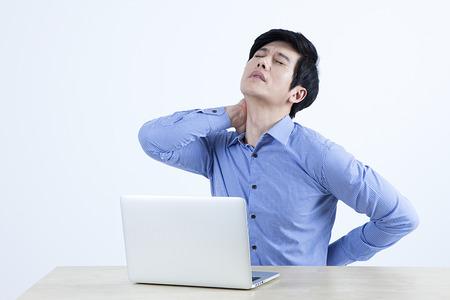 Photo pour Portrait of Asian man having neck pain because of laptop using isolated on white - image libre de droit