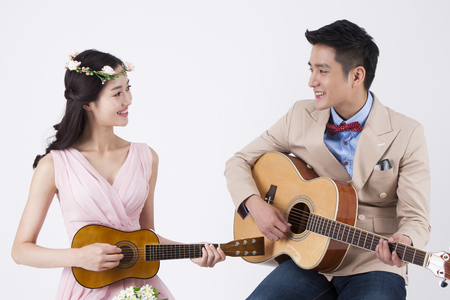 Photo for Asian happy couple playing guitar isolated on white - Royalty Free Image