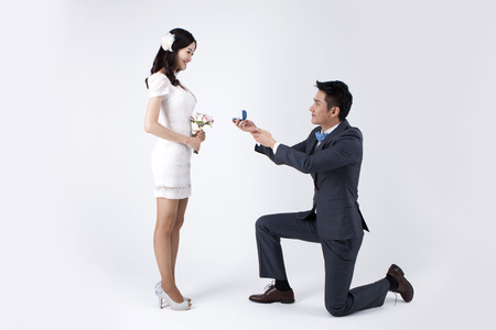 Photo pour Asian new married man giving ring while kneeling down isolated on white - image libre de droit