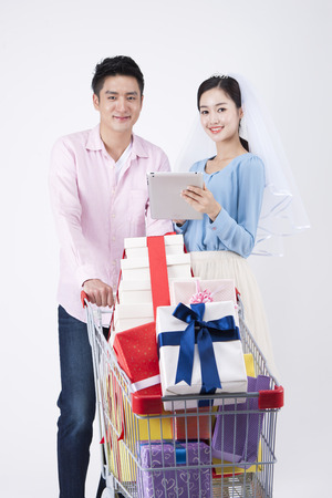 Photo for Asian happy couple with laptop and shopping cart isolated on white - Royalty Free Image