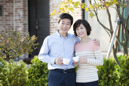 Foto de Asian middle aged couple drinking coffee outdoor - Imagen libre de derechos