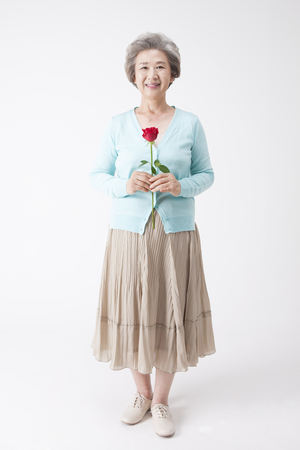 Photo pour Asian old aged woman with rose isolated on white - image libre de droit