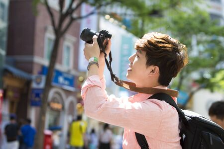 Photo for Asian tourist woman taking a picture in Seoul city street - Royalty Free Image