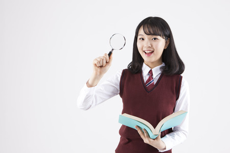 Foto de Asian female high school student with book and magnifier isolated on white - Imagen libre de derechos