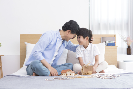 Photo for Asian grandfather and grandson playing with toy house - Royalty Free Image