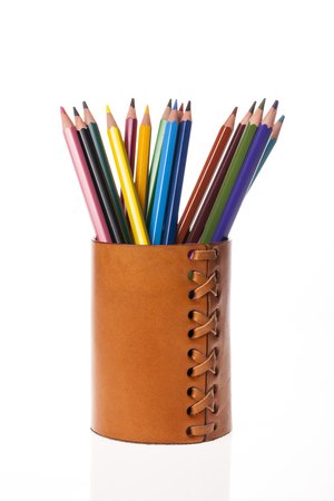 Photo for Colored pencils in a brown leather pen case isolated on white background - Royalty Free Image