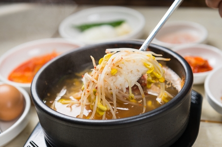 Foto de Spoon scooping up spicy bean sprout hangover soup, from black pot - Imagen libre de derechos