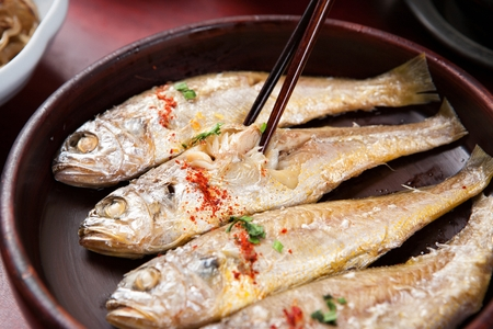 Photo pour Chopsticks picking up grilled yellow croaker with sprinkled chili powder and chives, on round plate - image libre de droit