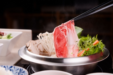 Photo pour Chopsticks picking up meat from shabu-shabu made of various vegetables such as mushrooms and pak choi, with glass noodles, in pot - image libre de droit