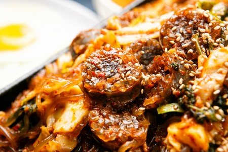Stir-fried vegetables,tripes and korean sausages with sprinkled perilla seeds on pan