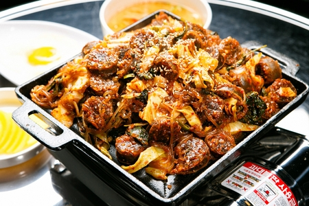 Stir-fried korean sausages and tripes with perilla leaves, in pan