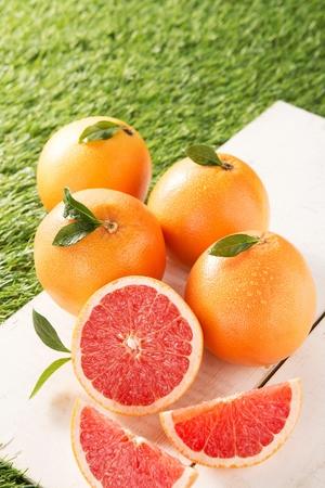 Photo pour sliced and whole grapefruits on wood panel, artificial grass - image libre de droit