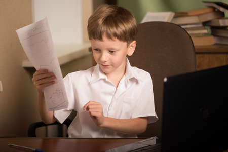 boy sitting at table with laptop and holding a sheet of paper