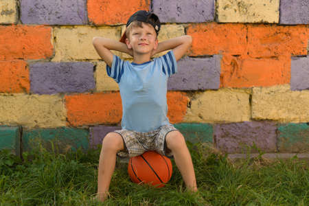 Photo for The guy with the ball sits on a natural grass cover. I sat down on a basketball ball resting after a difficult and exhausting game. Playground for children for basketball. - Royalty Free Image