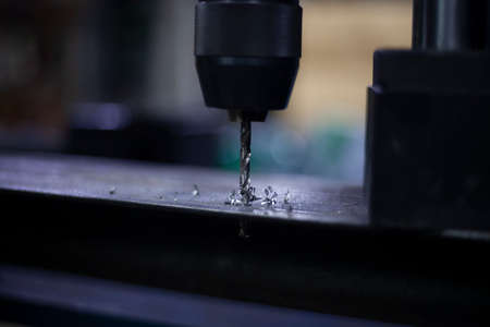 Foto de A modern drill for creating holes in metal. Work as a drill in the workshop. Replacing the drill after use. Preparing for work. Background is my hobby. Drill holes in a metal beam. - Imagen libre de derechos